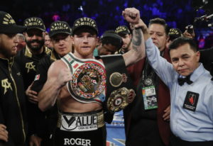 Canelo Alvarez poses for a photo with referee Benjy Esteves Jr., right, after defeating Gennady Golo