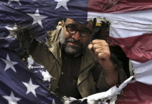 An Iranian protestor clenches his fist behind a burnt representation of the U.S. flag during a prote