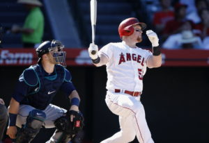 Los Angeles Angels' Kole Calhoun, right, hits a solo home run with Seattle Mariners catcher Mike Zun