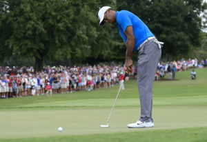 Tiger Woods putts for birdie on the third hole during the third round of the Tour Championship golf