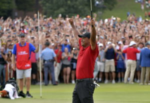 Tiger Woods celebrates after picking up his putt for par on the 18th green to win the final round of