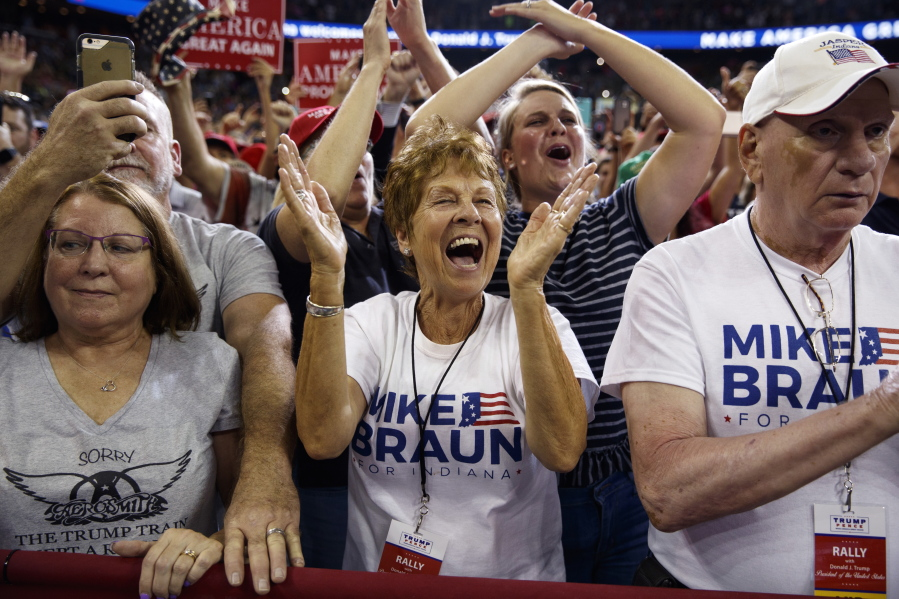Supporters of President Donald Trump wearing Mike Braun for Congress shirts cheer as he arrives