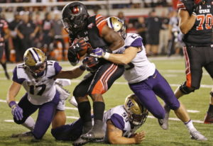 Utah running back Zack Moss (2) is tackled by Washington's Ben Burr-Kirven (25), Greg Gaines (99) an