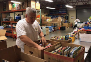 Northeast Hazel Dell: John Cameron organizing books for school shopping day at Share as part of D.A.
