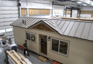 Wolf Industries employees work on one of the tiny modular homes at the company's new shop in Battle