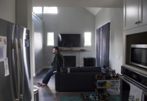 Tristan Graham, 32, sits on his couch in his new accessory dwelling unit, which was built in his par
