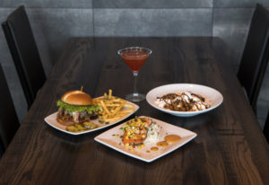 The Twigs Signature Burger with signature fries, clockwise from left, a Mango Pomegranate martini, t