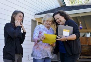 Homeowner Alice Jull of Vanport Rigging, center, receives documents during a follow-up visit from Ma