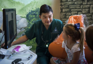 Dr. Ron Hsu looks over X-rays with patient Taryn Hatfield of Washougal, 6, center, and Taryn's mom L