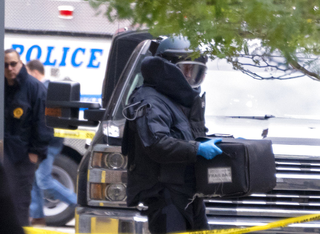 An NYPD bomb unit member holds a case containing a suspicious package discovered at a post office