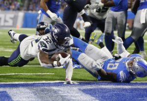 Seattle Seahawks running back Chris Carson (32) dives into the end zone for a 7-yard touchdown rush