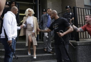 Rapper Cardi B is assisted by security guards as she leaves a police precinct Monday in the Queens b