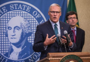 Gov. Jay Inslee addresses a news conference Thursday in Olympia with Attorney General Bob Ferguson f