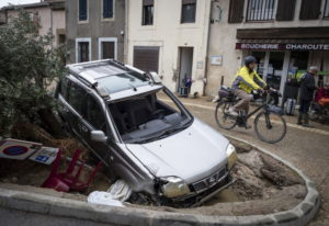A man rides past a damaged car in the town of Villegailhenc, southern France, Monday. Fred Lancelot/