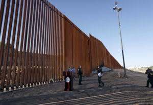 Border Patrol agents and others stand next to a new stretch of border wall in Calexico, Calif., Frid