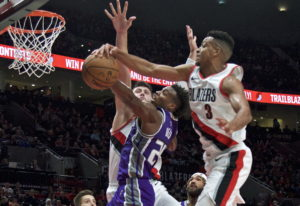 Sacramento Kings guard Buddy Hield, center, has a shot blocked by Portland Trail Blazers guard CJ Mc