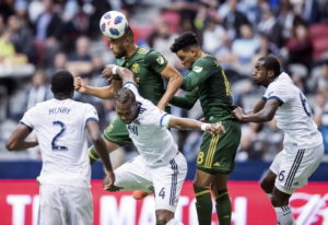 Portland Timbers' Bill Tuiloma, back left, gets his head on the ball in front of teammate Julio
