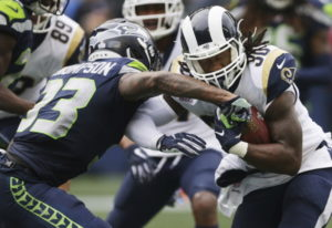 Los Angeles Rams running back Todd Gurley, right, powers past Seattle Seahawks free safety Tedric Th