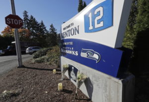 Flowers and candles rest near a sign for the Seattle Seahawks NFL football team headquarters Tuesday