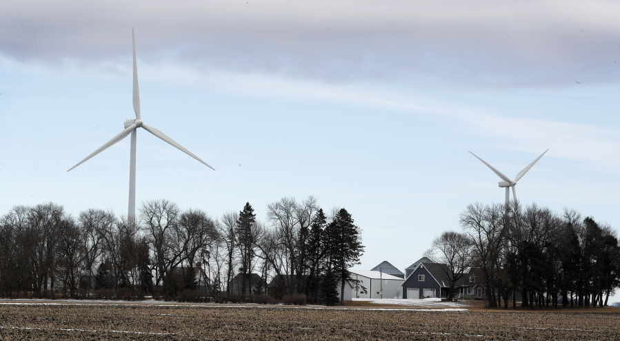 Wind turbines stand over a farmhouse near Northwood Iowa. A new study out of Harvard finds that ram