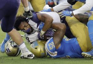Washington running back Myles Gaskin, top, loses his helmet as he is tackled by UCLA linebacker Loke