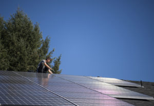 Simon Petersen, roof lead and apprentice electrician at Tesla, wires a solar array on the roof at Mi