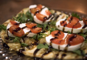 The flatbread at UnderBar is topped with caramelized onions, mozzarella cheese, arugula, tomato and