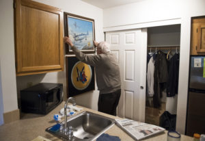 Bill Marshall rehangs a painting of the Republic P-47 Thunderbolt aircraft that he flew in World War