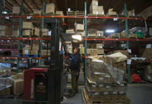 Cesar Hernandez of Price Mart, the warehouse in Portland used by Hi-School Pharmacy, helps distribut