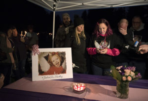 Nataasha Luchau, center, with pink sleeves, mother of Hartley Anderson, 5, reads a statement from th