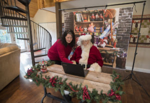 Kelly Stone, left, looks over WelcomeSanta.com with Jim Wood of Felida, also known as Santa Jim. Wel
