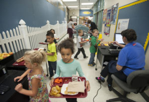 Kindergartners at Pleasant Valley Primary pick up lunch items and pay for their meals in a hallway b