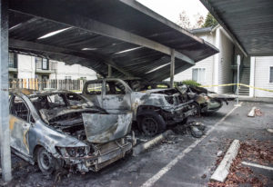 Cars damaged in an early morning car fire are seen here at the Meadow Wood Apartments on Wednesday m