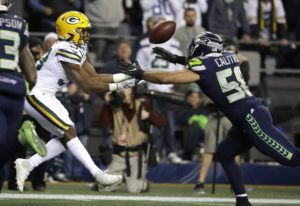 Green Bay Packers running back Aaron Jones, left, catches a pass for a touchdown, next to Seattle Se