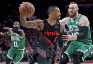 Portland Trail Blazers guard Damian Lillard, left, dribbles past Boston Celtics center Aron Baynes d