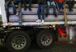 Central American migrants moving as a caravan toward the U.S. border get a free ride on a truck at I