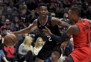 Los Angeles Clippers guard Shai Gilgeous-Alexander, left, tries to get past Portland Trail Blazers g