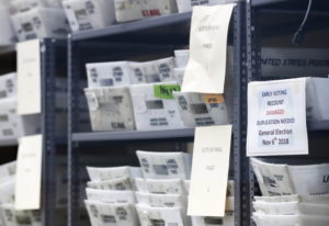 Bins filled with ballots are stacked at the Broward County Supervisor of Elections office as employe