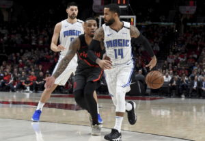 Orlando Magic guard D.J. Augustin, right, passes the ball behind his back to guard Evan Fournier, ba
