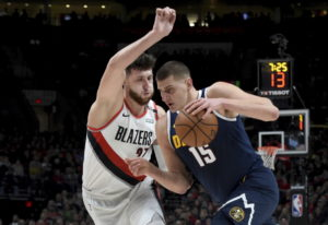 Denver Nuggets center Nikola Jokic, right, drives to the basket on Portland Trail Blazers center Jus