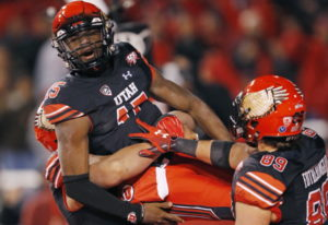Utah quarterback Jason Shelley (15) is hosted in the air by teammates after scoring against Oregon i