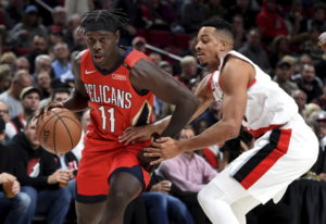 New Orleans Pelicans guard Jrue Holiday, left, drives to the basket on Portland Trail Blazers guard