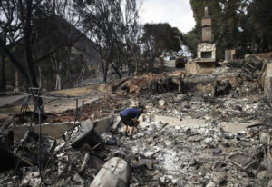 Roger Kelton searches through the remains of his mother-in-law's home leveled by the Woolsey Fire on