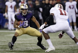 Washington's Myles Gaskin (9) carries as Stanford's Paulson Adebo moves in during the firs