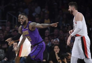 Los Angeles Lakers forward LeBron James, left, reacts to an inadvertent whistle by a referee as Port
