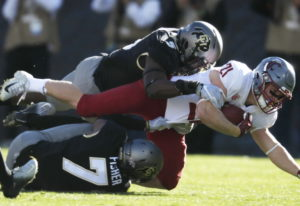 Washington State running back Max Borghi, center, is tackled after a short gain by Colorado lineback