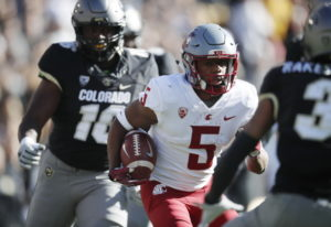 Washington State wide receiver Travell Harris, center, runs for a long gain past Colorado linebacker