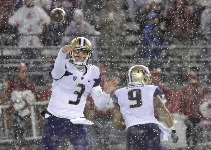 Washington quarterback Jake Browning passes as running back Myles Gaskin runs past him durin