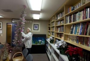Anthony Moreno, a volunteer, installs a Christmas tree inside the library at the Fort Vancouver Seaf