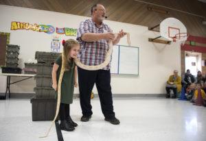 Scarlet Ferguson, Glenwood Heights Primary School kindergartener, lets a reticulated python rest aro